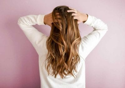 Girl Running Her Hands Through Naturally Curled Highlighted Hair