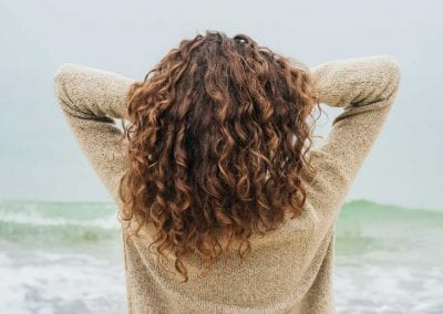 Women Running Hands Through Tightly Curled Brunette Hair
